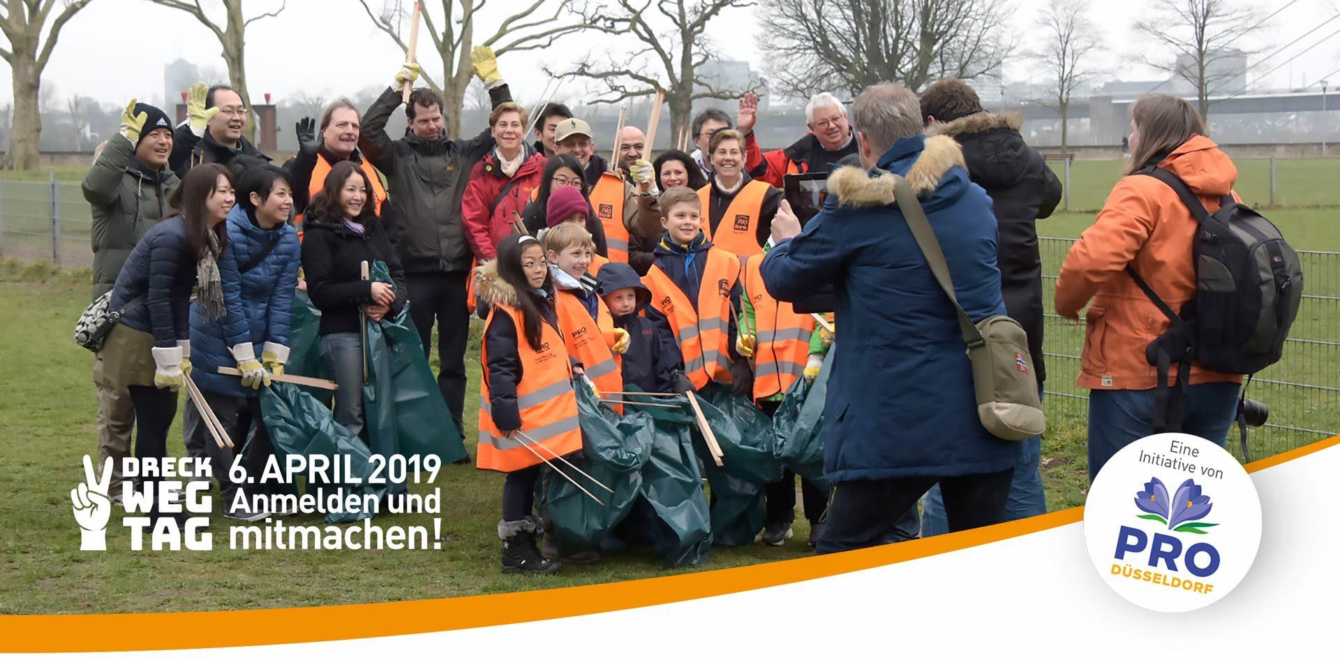 Gruppe von Kindern und Erwachsenen nehmen am Dreck-Weg-Tag teil