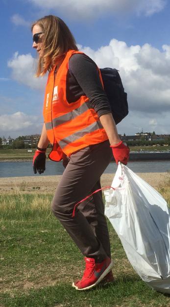 Teilnehmerin mit Handschuhen, Müllsack und Weste